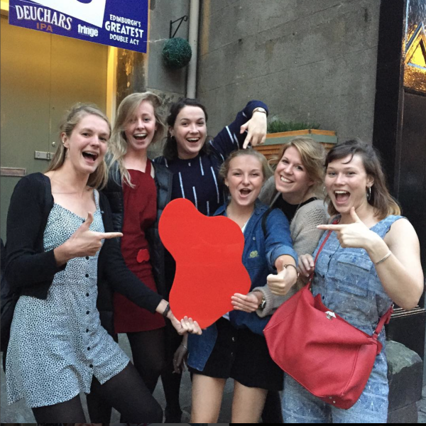group of white college-age women stood on stone steps outside an Edinburgh theatre venue posing with and pointing to a large red acrylic stains tm stain